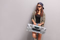 Cool teenage girl in hip hop outfit holding a radio ghetto blaster and leaning against gray wall Royalty Free Stock Photography