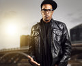 Cool urban african american man in glasses posing front of cityscape Stock Photos