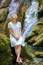Cool waterfall beautiful young woman in white sundress stopped to rest and dream near the among the mossy stones Royalty Free Stock Image