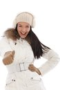 Cool woman with thumb up at wintertime smiling wearing white coat and knitted cap Stock Photo