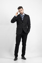 Cool young business man on the phone looking away full body length portrait over gray studio background Royalty Free Stock Image