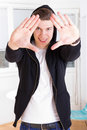 Cool young guy in hooded jacket framing his face with hands Royalty Free Stock Photo