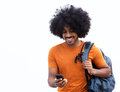 Cool young man with bag looking at mobile phone Royalty Free Stock Photo