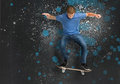 Cool young skateboarder doing an ollie trick on blue and grey paint splattered background Stock Images