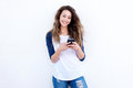 Cool young woman smiling with mobil phone against white background Royalty Free Stock Photo