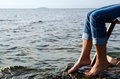 Cooling feet woman in the water sitting in a chair Royalty Free Stock Images