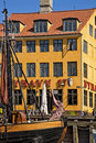Copenhagen, antique house with bright facade and old ship moored in Nyhavn Royalty Free Stock Photo
