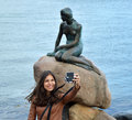 COPENHAGEN, DENMARK - MAY 31, 2017: tourist girl taking selfie photo with the bronze statue of the Little Mermaid, Den lille Havfr