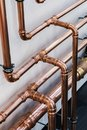 Copper pipe in front of a white wall Royalty Free Stock Photo