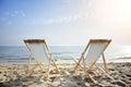 Coppie delle sedie sulla spiaggia sabbiosa al tramonto che cerca il concetto marino di rilassamento Fotografie Stock Libere da Diritti