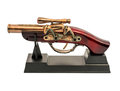 Copy of an old gun with wooden handle on a stand isolated on white background Royalty Free Stock Photo