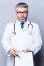 Copy space on his clipboard confident mature doctor looking at camera and pointing while standing isolated white Stock Image