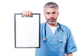 Copy space on his clipboard confident mature doctor looking at camera and showing with it while standing isolated white Stock Photos