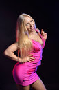Coquettish blonde in a pink dress flirtatious woman is posing and bending her sexy body she is wearing rosy sheath she is smiling Royalty Free Stock Photography