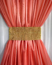 Coral curtain ruffled gold belt bright in the form of a bow gleaming on white tulle background Royalty Free Stock Image