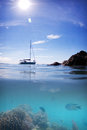 Coral reef fish boat sun water and sky split under over photograph of a feef anchored blue near a whitsunday island Royalty Free Stock Photography