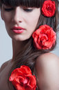 Coral roses in hair studio portrait of beautiful sensual young woman model with red lips elegant long brunette weaved into waves Stock Image