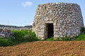 Corbelled stone hut a corbel led and a cultivated field with crops in the maltese countryside in the background is the island of Stock Image