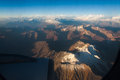 Cordillera de los andes the top of the ever snowy high mountains of in chile in the middle of the clouds litten by the orange Stock Photo