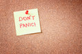 Cork board with pinned yellow note and the phrase dont panic written on it room for text Royalty Free Stock Photography