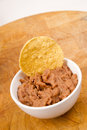 Corn chip buried in refried beans dish snack appetizer a dipped into ceramic ramekin Stock Photo