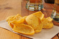 Corn chips and glasses of beer on a wooden bar counter Stock Images
