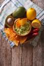 Corn chips, sauce guacamole and ingredients. vertical top view Royalty Free Stock Photo