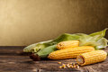 Corn cob and green leaves on rustic wooden table Royalty Free Stock Photography