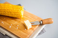 Corn cob on wooden board with pat of butter on corn skewer a hot the and a cold waiting to be put melted perfection Stock Photo