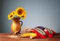 Corn in ethno bags and sunflowers in a ceramic vase Royalty Free Stock Photo