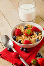 Corn flakes with berries on wooden table Stock Photo
