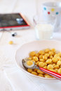 Corn flakes in bowl and milk tablet pc Royalty Free Stock Photography
