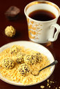 Corn flakes chocolate truffles on a plate with a cup of tea on a dark background Stock Photo