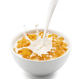 Corn flakes with milk splash pouring into creating Stock Photography