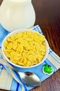 Corn flakes with milk yellow in a jug spoon napkin against a wooden board Stock Photography