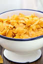 Corn flakes in white bowl on brown background Royalty Free Stock Photo