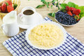 Corn porridge with milk, a Cup of coffee and the berries of honeysuckle and strawberries. Royalty Free Stock Photo