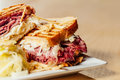 Corned beef and pastrami sandwich with swiss cheese sauerkraut with a side of potato sticks clear pickle slaw Royalty Free Stock Photos