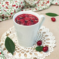Cornel jam close up of cup with on crocheted napkin square image Stock Photos