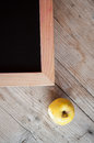 Corner of blank school chalkboard with a yellow apple near her Stock Images