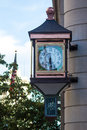 Corner clock old fashioned constructed from copper stained glass and metal hanging on the of a building Royalty Free Stock Image