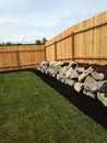 Corner fence of small fenced backyard with rock wall grass area Royalty Free Stock Images