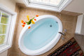 Corner oval bathtub full of clean water sunken into a brown tile surround and flanked by two tall view windows overhead view Stock Photos