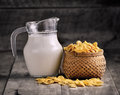 Cornflakes in basket and glass of milk on wooden table