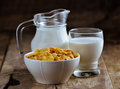 Cornflakes in bowl and glass of milk on wooden table