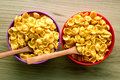 Cornflakes in small bowls with wooden spoons Royalty Free Stock Photo