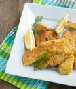 Cornmeal crusted tilapia served in plate with lemon Royalty Free Stock Photography