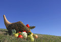 Cornucopia against blue sky with fruits and vegetables on grass field Stock Images