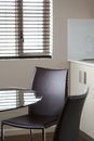 Corporate boardroom chair and glass table window in background with blinds Royalty Free Stock Images