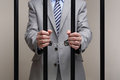 Corporate crime businessman behind bars in prison concept for white collar Royalty Free Stock Image